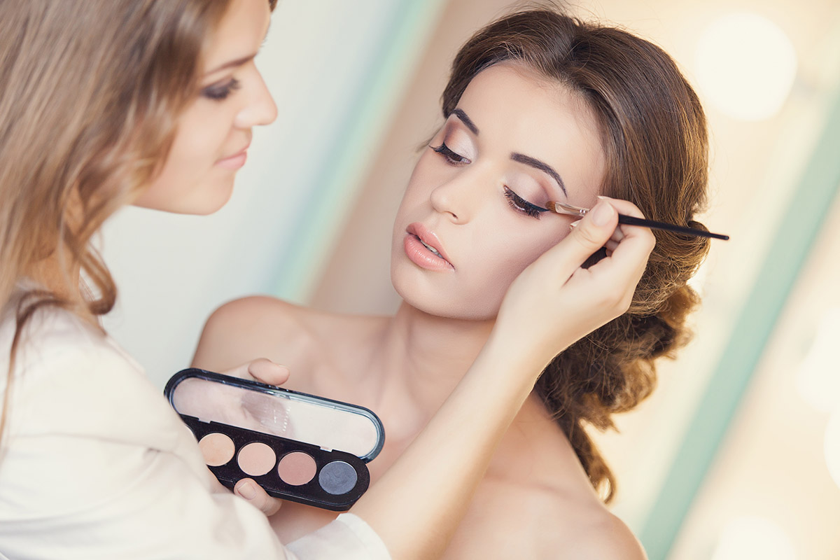 Beautiful bride applying wedding make-up by professional make-up artist on the wedding day photo via Shutterstock