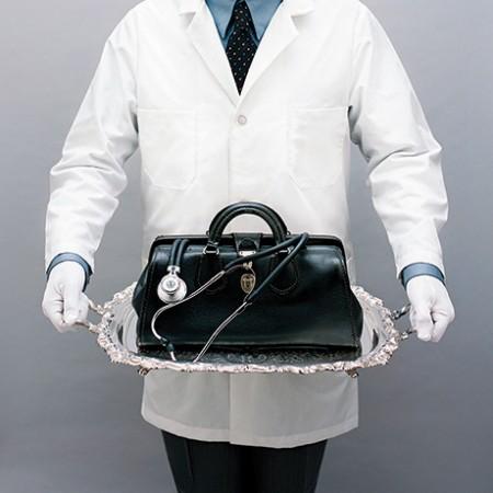 Doctor with white gloves serving medical bag on silver platter