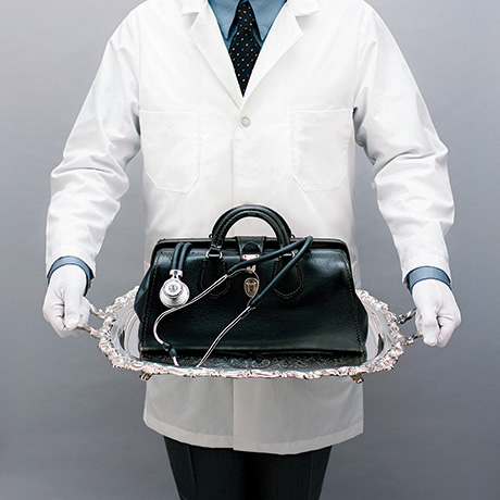 Doctor with white gloves serving medical bag on silver platter