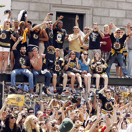 Boston Bruins fans cheer from on top of a bus stop in Copley Square as a duck boat carrying Bruins players goes by during a parade honoring NHL hockey's Stanley Cup Champions Saturday, June 18, 2011 in Boston. (AP Photo/Winslow Townson)