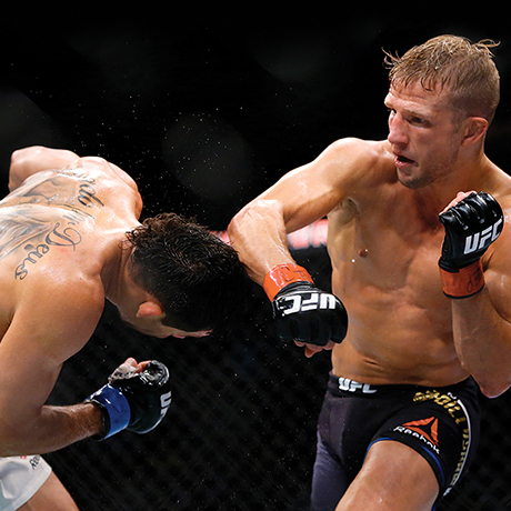 TJ Dillashaw, right, lands a punch to the head of Renan Barao during their bantamweight mixed martial arts title bout during UFC Chicago on Saturday, July 25, 2015, in Chicago. Dillashaw won in the fourth round. (AP Photo/Jeff Haynes)