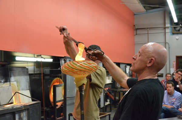 Two glassblowers work on a project as a class watches at Diablo Glass School.