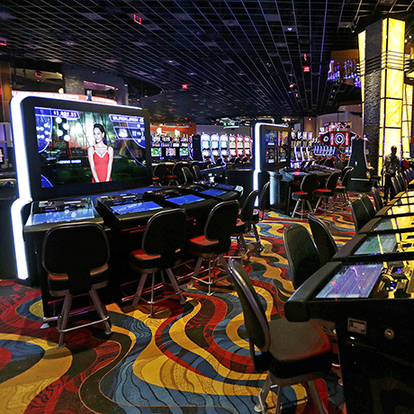 Slot machine lights glow on the floor of the Plainridge Park Casino in Plainville, Mass., Tuesday, June 23, 2015. The casino, a slot machine parlor, is scheduled to open on Wednesday June, 24, 2015. The Plainridge Park Casino represents the first gambling destination to open since state lawmakers approved a casino law in 2011. (AP Photo/Charles Krupa)