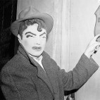 A newsman wears a rubber mask similar to that worn by seven bandits who robbed Brink's armored car firm in Boston of $1, 50,000, Jan. 18, 1950. The reporter points to name plate on first of six locked doors opened by the gunmen. Mask was one of several purchased in joke shops by newsmen and police to see if they resembled description given by Brink's employees. (AP Photo)
