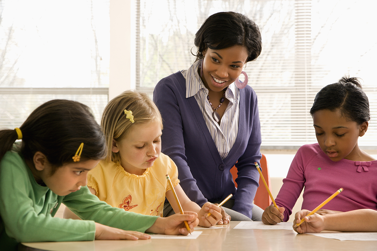 Teacher helping students in school classroom via Shutterstock