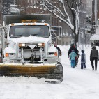 Plows clear Charles Street in Boston, Sunday, Feb. 15, 2015. A blizzard warning was in effect for coastal communities from Rhode Island to Maine, promising heavy snow and powerful winds to heap more misery on a region that has already seen more than 6 feet of snow in some areas. (AP Photo/Michael Dwyer)