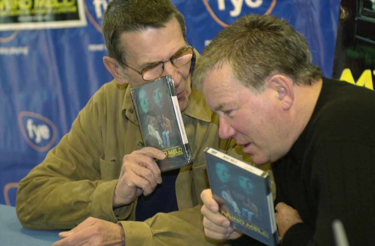 """Leonard Nimoy, left, and William Shatner talk privately while autographing copies of their recently released DVD/VHS """"Mind Meld: Secrets Behind the Voyage of a Lifetime"""", Sunday, March 17, 2002, in the Century City section of Los Angeles. Mind Meld is an examination of the impact the Star Trek experience has had on the franchise's two most celebrated participants. (AP Photo/Ric Francis)"""