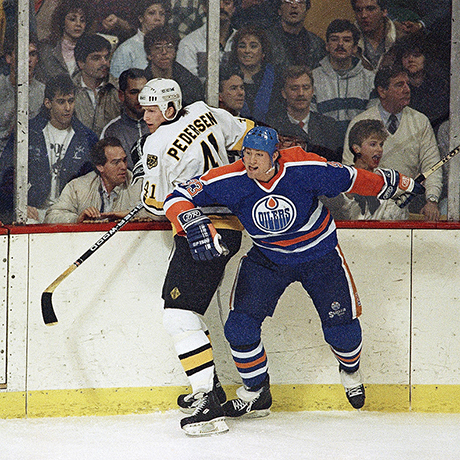 Boston Bruins Allen Pedersen, left, gets checked against the boards by Edmonton Oilers Marty McSorley in early first period action of their N.H.L. game at Boston Garden on Monday, Jan. 4, 1988. (AP Photo/Jim Gerberich)