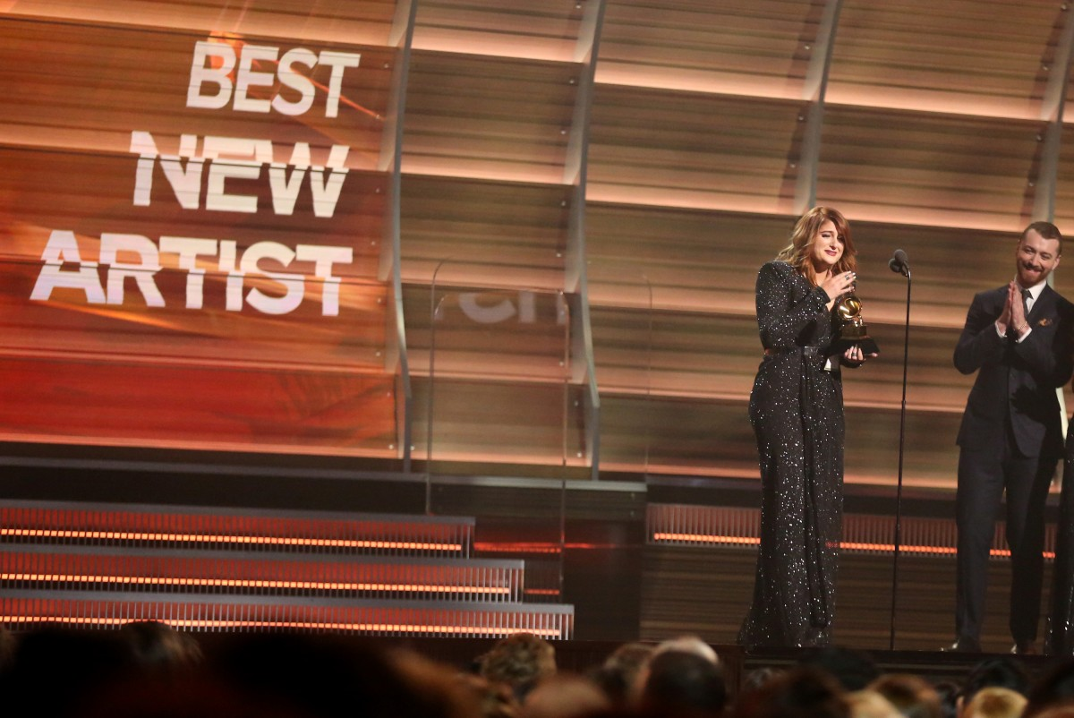 Sam Smith, right, looks on as Meghan Trainor accepts the award for best new artist at the 58th annual Grammy Awards on Monday, Feb. 15, 2016, in Los Angeles. (Photo by Matt Sayles/Invision/AP)