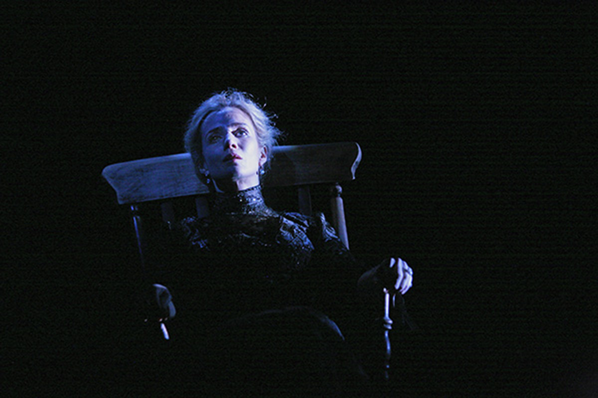 Lisa Dawns sits in a rocking chair on a dark stage