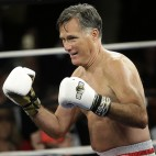 Former Republican presidential candidate Mitt Romney walks to the center of the ring before sparring with five-time heavyweight boxing champion Evander Holyfield at a charity fight night event Friday, May 15, 2015, in Salt Lake City. The black-tie event will raise money for the Utah-based organization CharityVision, which helps doctors in developing countries perform surgeries to restore vision in people with curable blindness. (AP Photo/Rick Bowmer)
