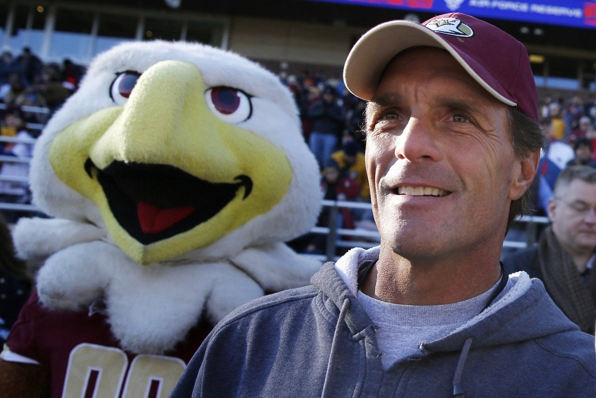 """Former Boston College quarterback Doug Flutie stands on the sidelines next to the team mascot after being honored on the 30th anniversary of the 1984 team's """"Miracle in Miami"""" during an NCAA college football game against Syracuse in Boston, Saturday, Nov. 29, 2014. Boston College won 28-7. (AP Photo/Michael Dwyer)"""