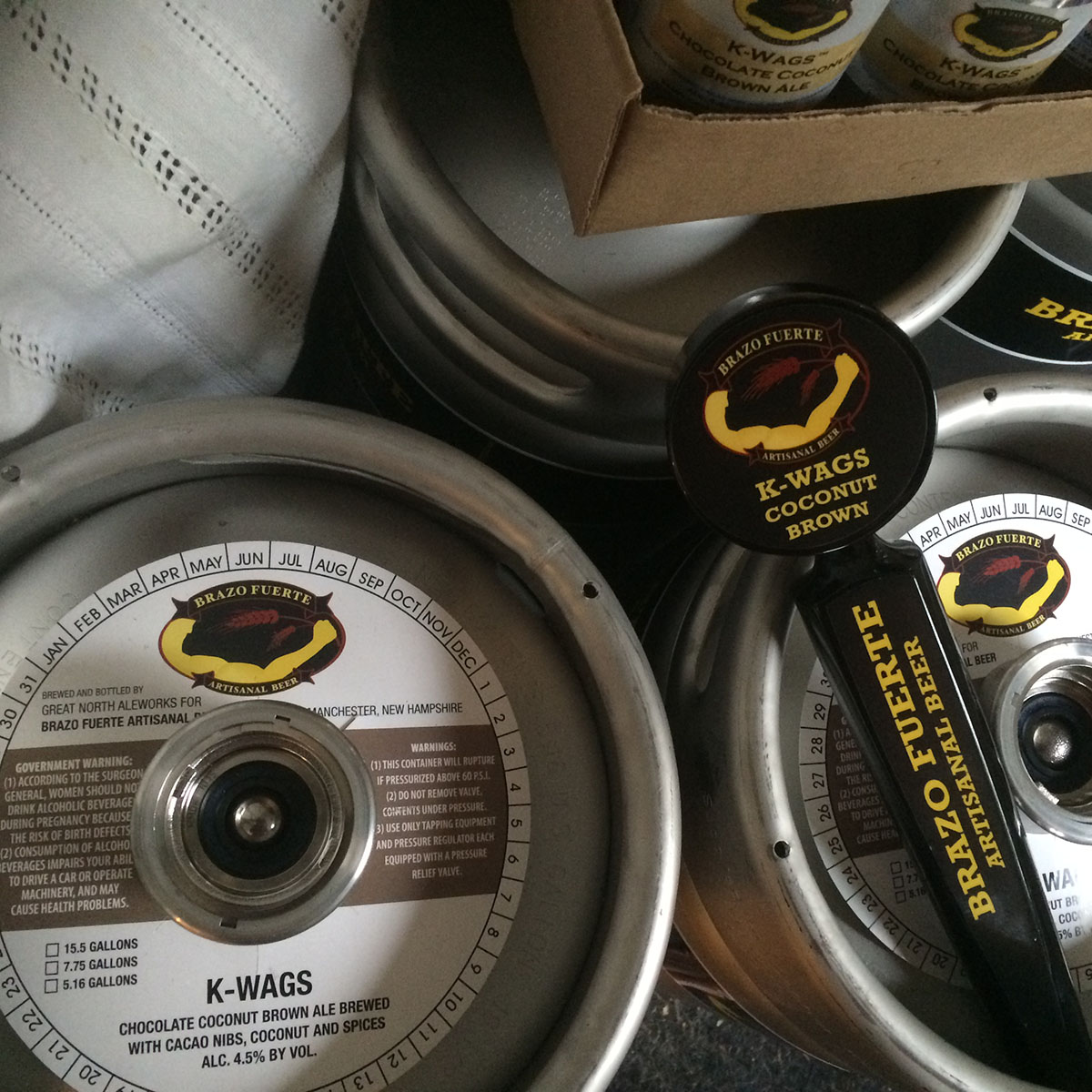 Kegs, cans, and tap handles for Brazo Fuerte's K-Wags chocolate ale