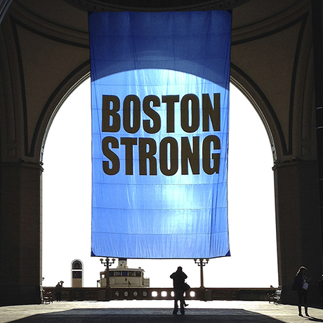 People stop to photograph a Boston Strong banner hanging at Rowes Wharf on Friday, April 15, 2016, in Boston, to commemorate the third anniversary of the Boston Marathon bombings. (AP Photo/Bill Sikes)