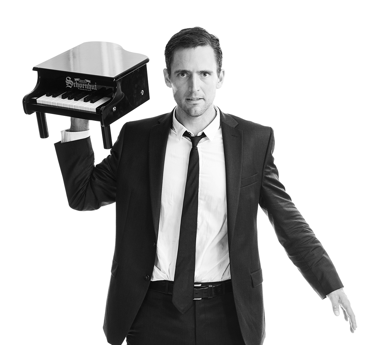 Owen Benjamin holds a piano in his headshot.