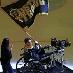 Actor Jake Gyllenhaal, portraying Boston Marathon bombing survivor Jeff Bauman, waves a flag while filming a scene from an upcoming feature film about the bombing on the ice of Boston Garden, Tuesday, April 5, 2016. (AP Photo/Charles Krupa)