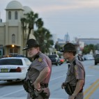 Members of the Florida Highway Patrol continue to block Orange Ave near the Pulse Orlando nightclub before sunrise Monday, June 13, 2016, in Orlando, Fla. Pulse Orlando was the scene of a mass fatal shooting early Sunday morning. (AP Photo/Chris O'Meara)