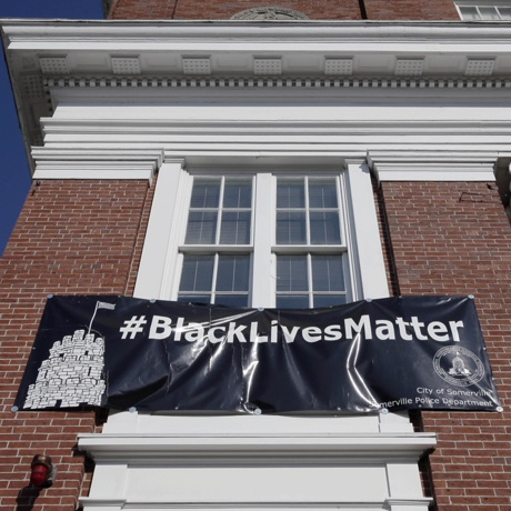 """A """"Black Lives Matter"""" banner hangs at the main entrance of City Hall Thursday, July 21, 2016, in Somerville, Mass. Somerville's mayor denied a request from police officers that the banner, which has hung for nearly a year, be removed and replaced with one that says """"All Lives Matter."""" (AP Photo/Steven Senne)"""