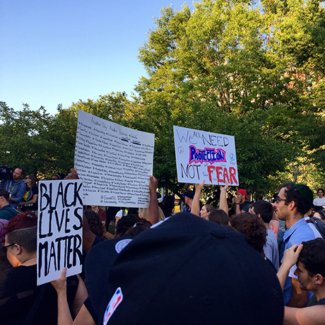 feature protestors hold signs reading %22black lives matter%22 and %22we need protection not fear%22