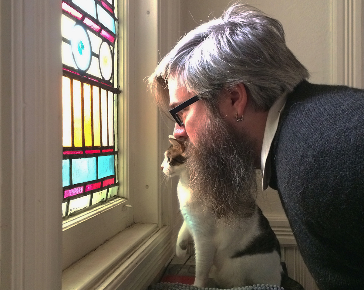 Sheridan and his cat watch from a window. / Photo provided by Boon Sheridan
