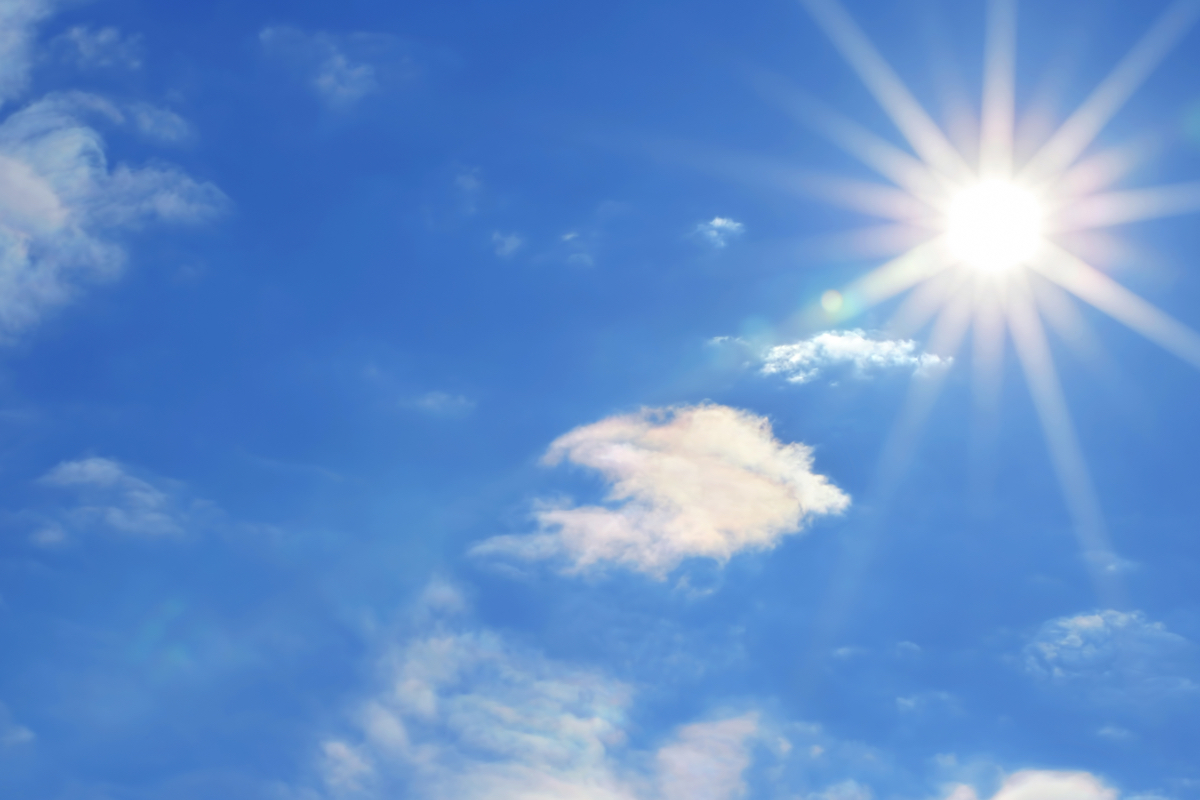Bright sun with beautiful beams in a blue sky with light clouds. Much space for copy.