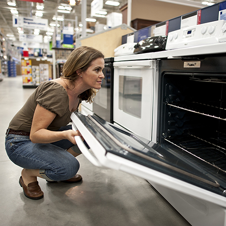 Caucasian mature housewife shopping for a new kitchen stove in a huge hardware store