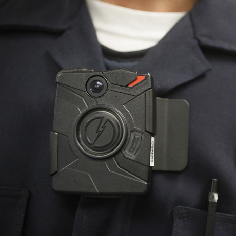 """FILE - In this Jan. 15, 2014 file photo, a Los Angeles Police officer wears an on-body camera during a demonstration for media in Los Angeles. The fatal police shooting of the unarmed black teenager in Ferguson, Mo. has prompted calls for more officers to wear so-called """"body cameras,"""" simple, lapel-mounted gadgets that record the interactions between the public and law enforcement. (AP Photo/Damian Dovarganes, File)"""