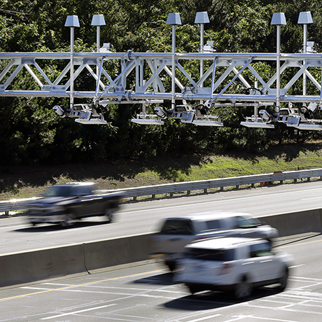 Cars pass under toll sensor gantries hanging over the Massachusetts Turnpike, Monday, Aug. 22, 2016, in Newton, Mass. The state Department of Transportation is discussing plans for demolishing the tollbooths as it gets ready to implement an all-electronic tolling system on Interstate 90 which runs the length of the state. (AP Photo/Elise Amendola)