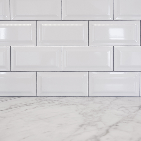 a subway tile backsplash with marble countertop in a modern kitchen