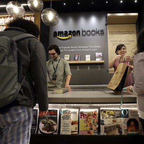 Clerks check-out some of the first customers at the opening day for Amazon Books, the first brick-and-mortar retail store for online retail giant Amazon, Tuesday, Nov. 3, 2015, in Seattle. The company says the Seattle store, coming two decades after it began selling books over the Internet, will be a physical extension of its website, combining the benefits of online and traditional book shopping. (AP Photo/Elaine Thompson)