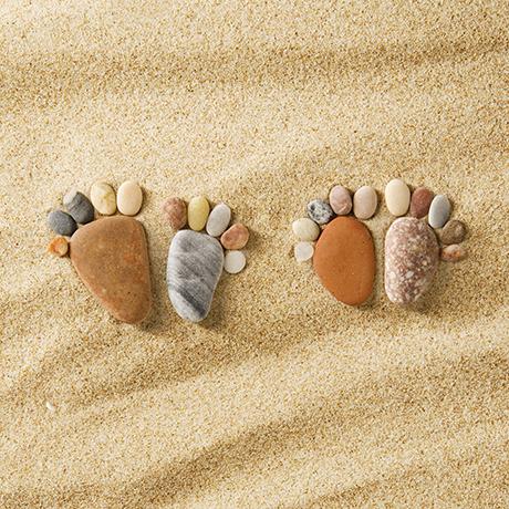 Stone arranged like footprints on the beach