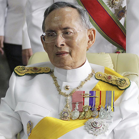 FILE - In this Dec. 5, 2011, file photo, Thailand's King Bhumibol Adulyadej is pushed on a wheelchair while leaving Siriraj hospital for the Grand Palace for a ceremony celebrating his birthday in Bangkok. Hundreds of tearful Thais on Thursday, Oct. 13, 2016, were continuing to offer flowers and chant prayers for King Bhumibol Adulyadej outside the Bangkok hospital where the world's longest-reigning monarch is being treated for multiple health problems. (AP Photo/Apichart Weerawong, File)