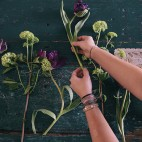 Florist workspace: woman making floral decorations; flowers on a old wooden table