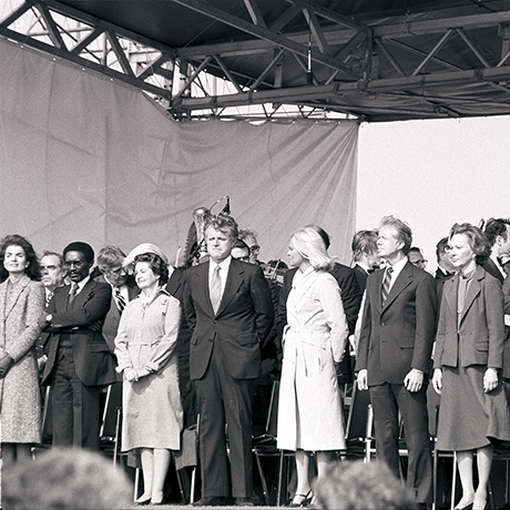 NLK79-40:31                           20 Oct. 1979  Dedication of the John F. Kennedy Presidential Library and Museum, Boston MA. Front row: Jacqueline Bouvier Kennedy, Unidentified, Lady Bird Johnson, Senator Edward M. Kennedy, Joan Kennedy, President Jimmy Carter, Roslyn Carter, Humberto Cardinol Medeiros, unidentified, unidentified. Also in photo: Speaker of the House, John W. McCormack. Harry Ellis Dickson (back to camera) conducts the Boston Pops Esplanade Orchestra.