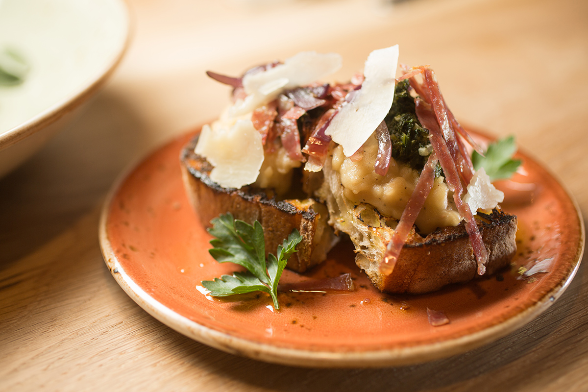 Soppressata and white bean bruschetta with grilled red onion, fennel pollen and pecorino. / Photo by Erik Jacobs / JacobsPhotographic