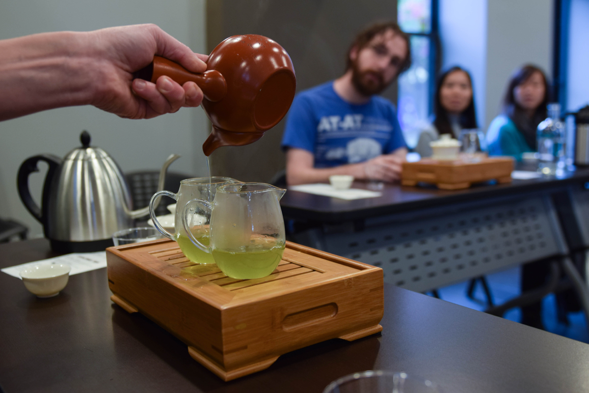 Scalise uses a Japanese Kyusu to pour Gyokuro, a seaweed-y tasting Japanese green tea, into two pitchers. The wooden contraption they're sitting on is a tea boat, which holds water to rinse the equipment and catches any spills. / Photo by Lloyd Mallison