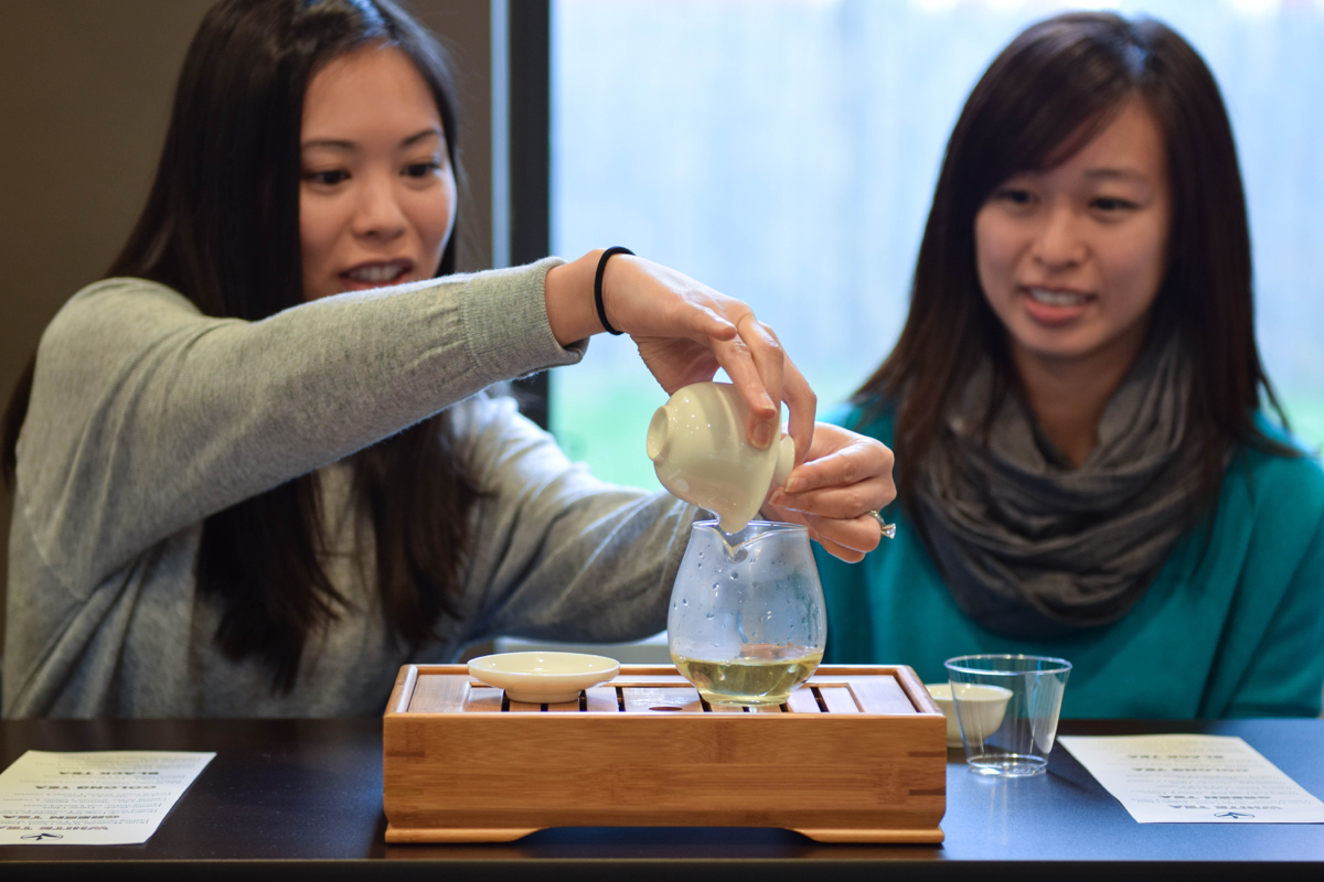 Tea fans Cathy Sze and Lori Lee try to replicate Scalise's pour from the Gaiwan, a Chinese lidded bowl used for infusing tea leaves. / Photo by Lloyd Mallison