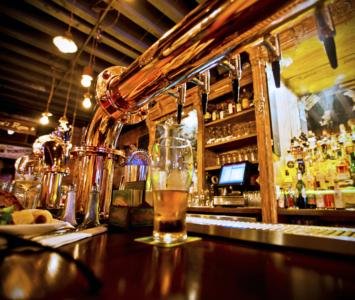 Glass of beer and beer taps in a bar
