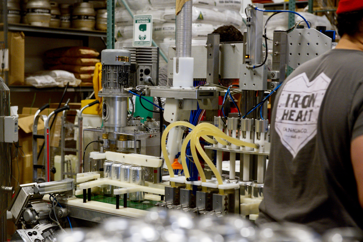 Beer is pumped into 16-ounce cans before they're automatically sealed shut. / Photos by Lloyd Mallison