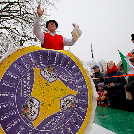 Peter Lovis, proprietor of the Concord Cheese Shop, announces the arrival of a 400-pound wheel of Crucolo cheese (front) at his shop in Concord, Massachusetts December 5, 2013.  This was the fourth annual Crucolo Parade, organized by Lovis and ending with free samples of the cheese for the crowd gathered to watch the parade.   REUTERS/Brian Snyder  (UNITED STATES)