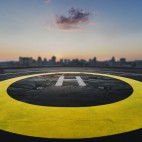 Helipad on the roof of a skyscraper after raining with cityscape view and sunset