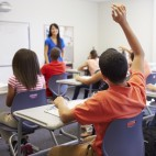 Female High School Teacher Taking Class Raising Hand