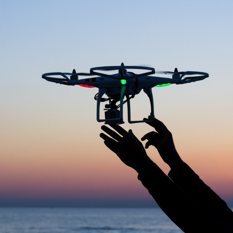 Viareggio, Italy - October 30, 2014: Drone takes off from the operator's hand with camera at sunset Quadcopter industry is told to be growing at triple digitsevery year, for a market expected to pass the 20 billion in the 2020. The dji is a chinese company leader of quadcopter industry, and the phantom is expected to be the top seller gift for christmas 2015