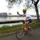 Democratic Presidential candidate Sen. John Kerry, D-Mass., raises a fist to members of the media pool as he bikes along the Esplanade in Boston Thursday, July 29, 2004. Kerry will be delivering his speech to the Democratic National Convention tonight. (AP Photo/Gerald Herbert)