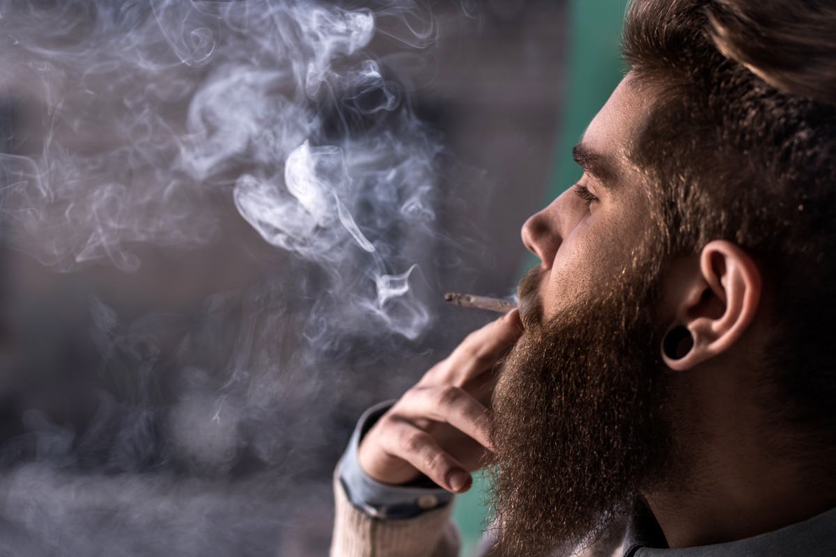 Close up of hipster man smoking weed cigarette.