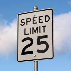 A 25 MPH speed limit sign highlighted by a blue sky in the background.