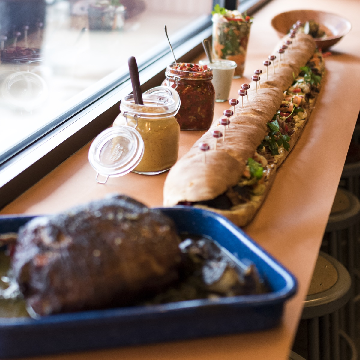 Roasted pork shoulder with fennel and broccoli rabe, Sweet Cheeks condiments, and a 5-Foot Pork Bomb