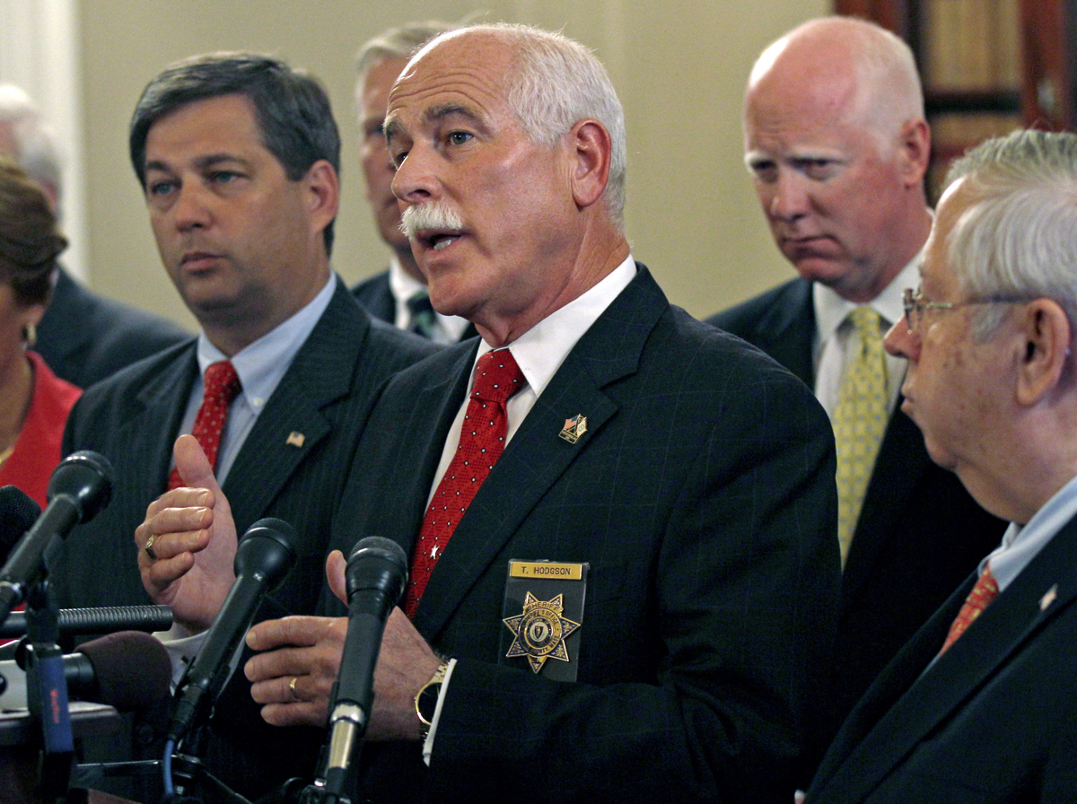 """Bristol County Sheriff Thomas Hodgson gestures during a news conference in regard to the """"Secure Communities"""" program, or """"S Comm"""", held by Massachusetts county sheriffs at the Statehouse in Boston, Wednesday, Sept. 28, 2011. The program is designed to immediately check the immigration status of those arrested for crimes. Opponents say it will lead to profiling.(AP Photo/Charles Krupa)"""