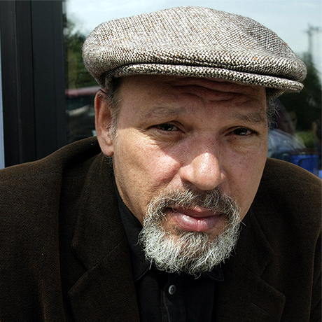 "Pulitzer Prize-winning playwright August Wilson poses during a visit to a coffee shop Friday, May 30, 2003, in his Seattle neighborhood. After more than two decades in theater, Wilson finally has the acting bug, making his stage debut two weeks ago in his autobiographical monologue, ""How I Learned What I Learned,"" and he will make his movie debut this month as narrator of ""The Naked Proof,"" an independent film premiering at the Seattle International Film Festival. (AP Photo/Ted S. Warren)"