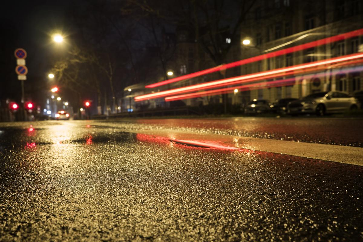 Wet asphalt tail lights motion blur - low-angle view